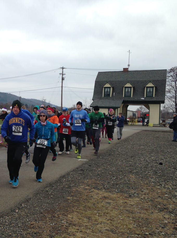 Runners take off from the start line of the Christmas Cookie Run at the Vestal Coal House.