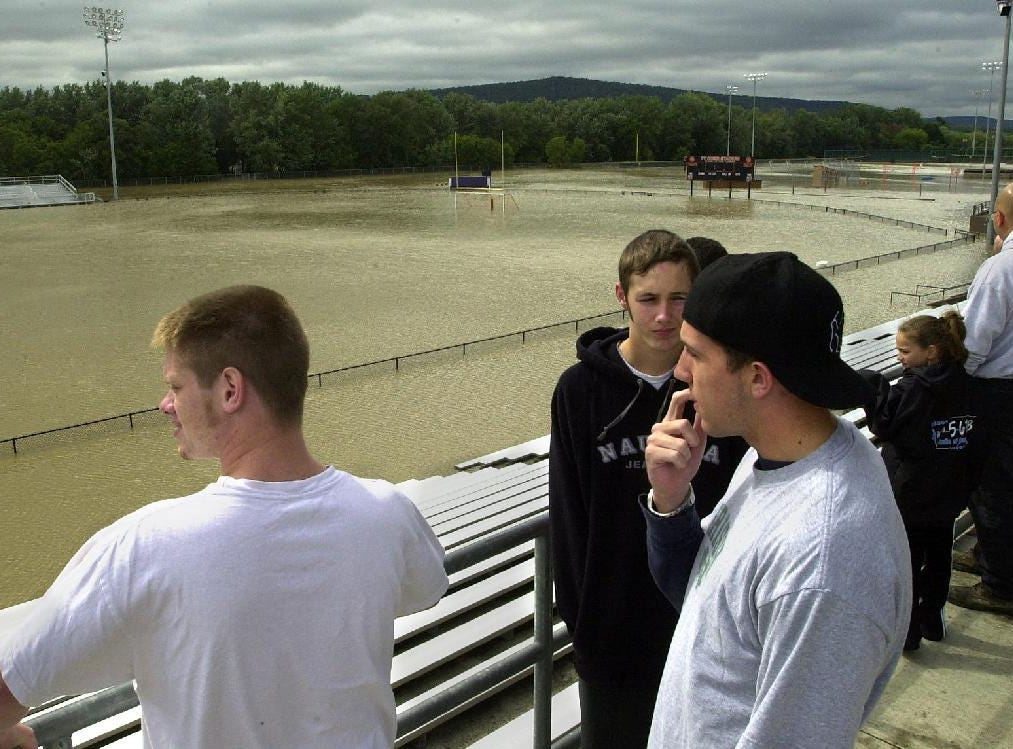 From 2004: Union-Endicott Varsity Football players, from left, Chris Locke, 18, Sean Quinlivan, 17 and Chris Kline, 17, overlook the flooded football field behind the high school Saturday that force the cancellation of their game. Both the field and locker rooms are under a couple of feet of water.