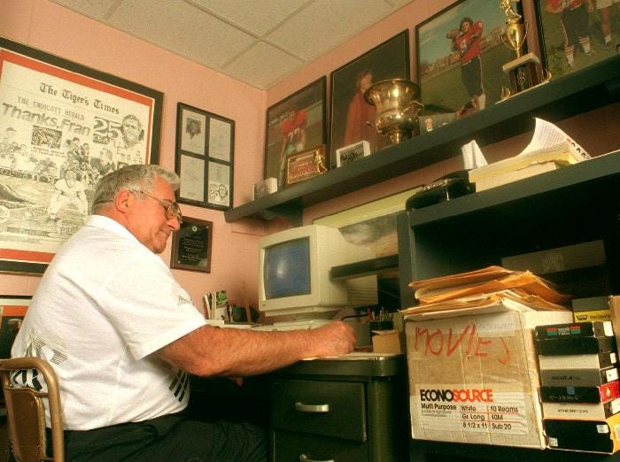 Former Union-Endicott football coach Fran Angeline flips through manuscripts at his desk in the championship room at his Endicott home in 1996.