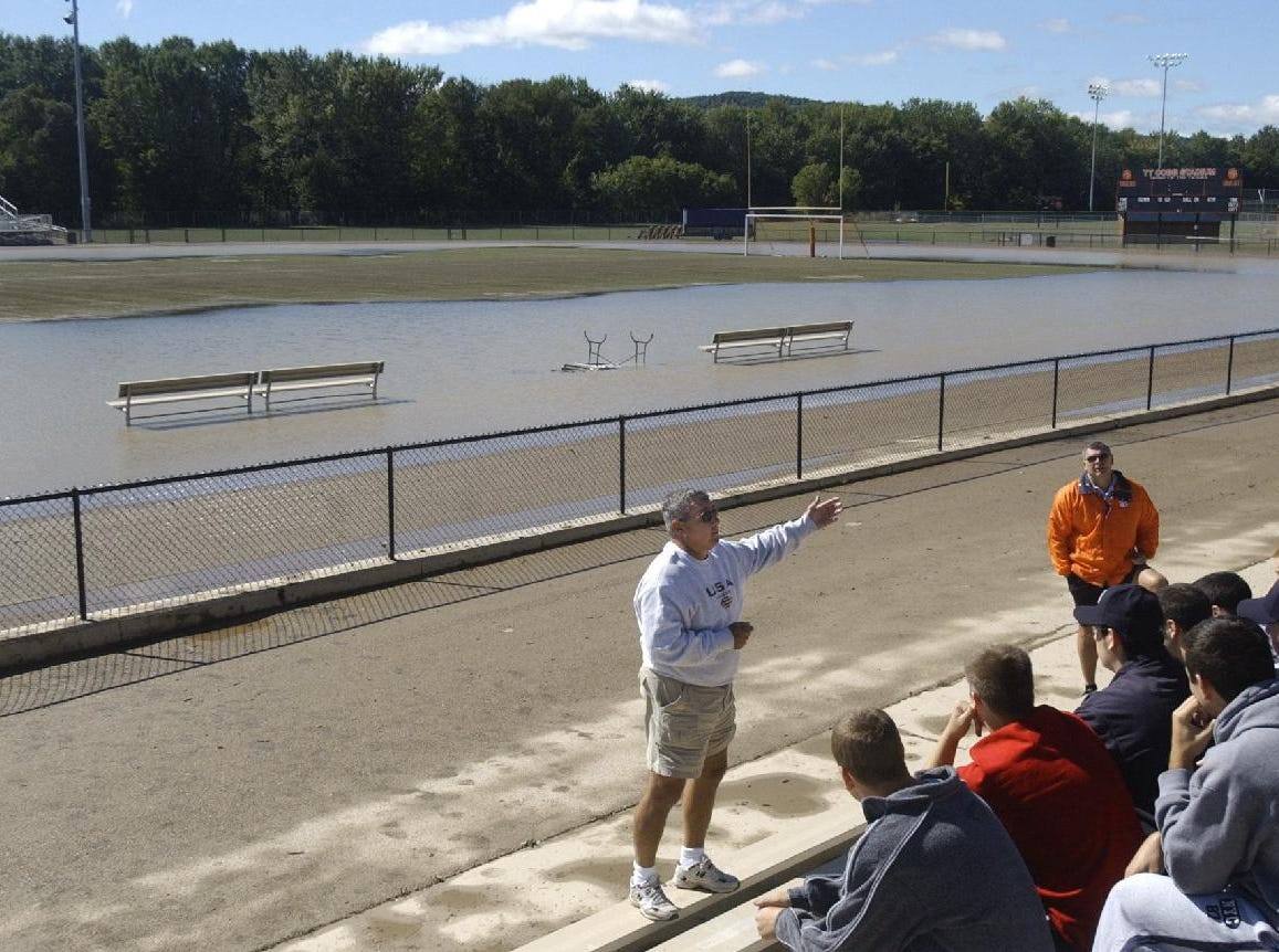 From 2004: Union-Endicott football coach Bart Guccia, left, and Athletic Director Al Brunetti, right, meet with the football team Sunday morning at Union-Endicott football stadium to discuss plans concerning the location of their practices and games for the rest of season after high waters damaged their playing field.