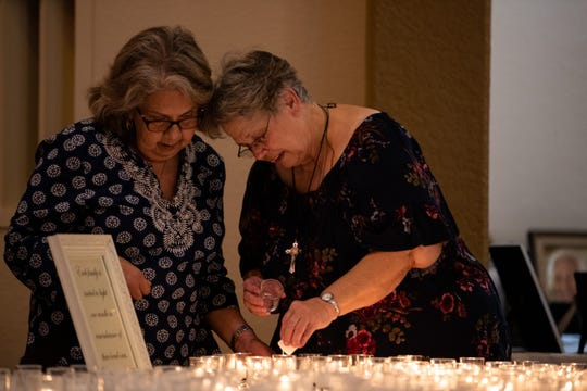 Two women light a candle during the All Soul's Day mass in the Seaside Funeral Home Chapel on Friday, Nov. 2, 2018.