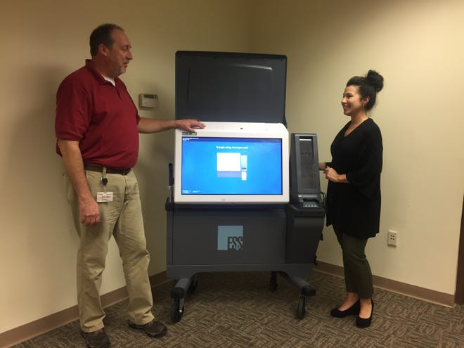 Mark Harris, director of election operations, and Stephanie Salvatore, superintendent of elections, demonstrate new voting machines that will be used in National Park Tuesday.