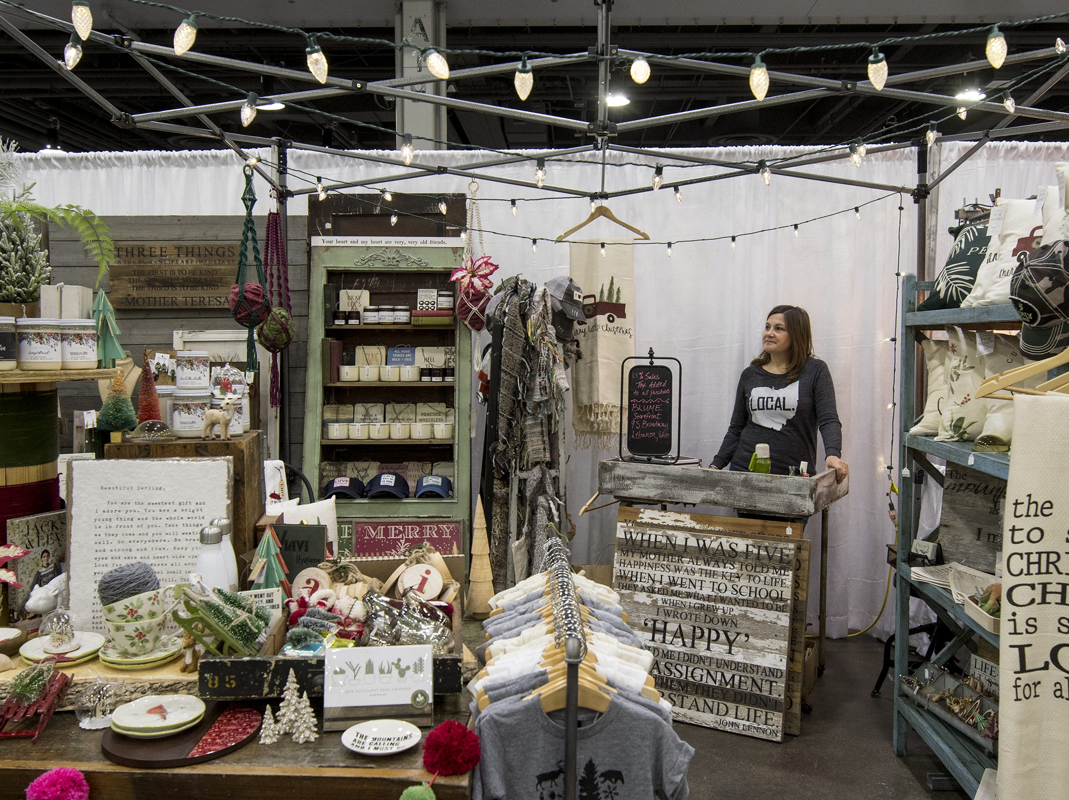 Amanda Marsh of Blume, stands in her decorated booth during the Greater Cincinnati Holiday Market at the Duke Energy Center Friday, November 2, 2018 in Cincinnati, Ohio. The event runs through Sunday, November 4.