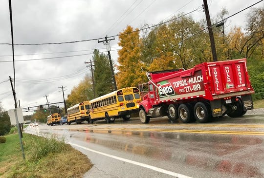 An Evans Landscaping truck brings up the rear of a line of Forest Hills Local School District buses traveling down Round Bottom Road in Newtown Nov. 1, 2018.