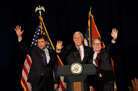 U.S Rep. Troy Balderson, left to right, Vice President Mike Pence and gubernatorial candidate Mike DeWine wave to supporters at the Mansfield Lahm Regional Airport, Wednesday, Oct. 31, 2018, in Mansfield, Ohio. (AP Photo/Tony Dejak)