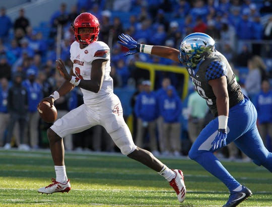Louisville Cardinals quarterback Lamar Jackson (8) runs the ball against Kentucky Wildcats Kentucky Wildcats linebacker Alex King (58) during the game at Commonwealth Stadium. Louisville defeat Kentucky 44-17.