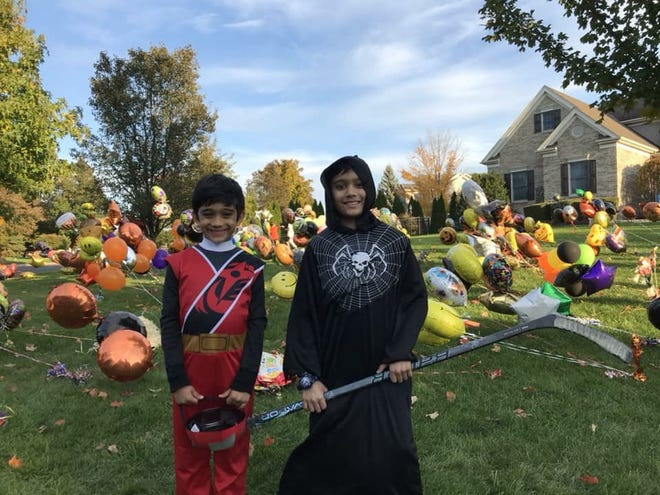 Arjun Jain (right) with his brother Krish on the front lawn of their Hillsborough home. On Halloween, balloons were put on the lawn to support Arjun's fight against leukemia.