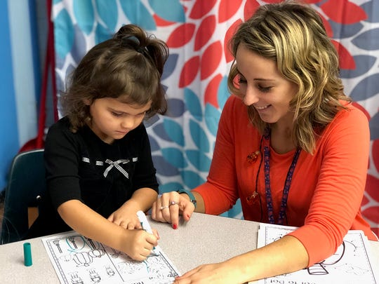 Amber Lillibridge Lonsinger works with a student on a coloring page for Halloween at Sacred Heart Catholic School.