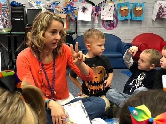 Amber Lonsinger encourages her students to choose their favorite character after reading them a Halloween story.