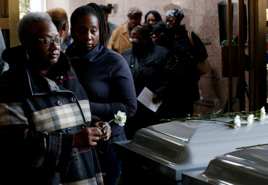 People walk by to lay flowers on the caskets containing the cremated remains of their loved ones during an All Souls' Day memorial service at Mt. Olivet Cemetery in Detroit on Friday, November 2, 2018.