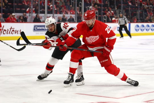 Mike Green #25 of the Detroit Red Wings battles for the puck with Jean-Sebastien Dea #10 of the New Jersey Devils during the first period at Little Caesars Arena on November 1, 2018 in Detroit, Michigan.