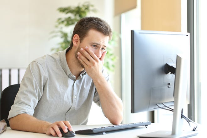 Worried man working trying to solve troubles on line with a desktop computer at office