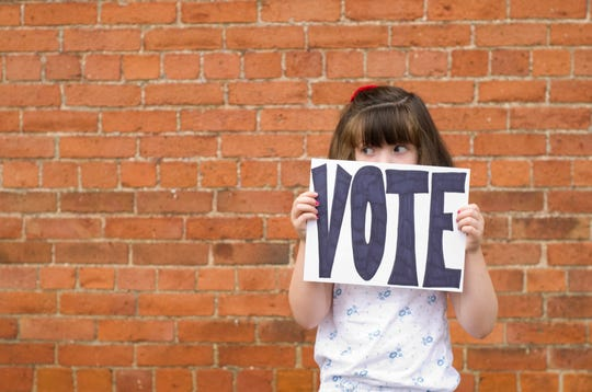 A little girl peeks over a sign that reminds people to vote.