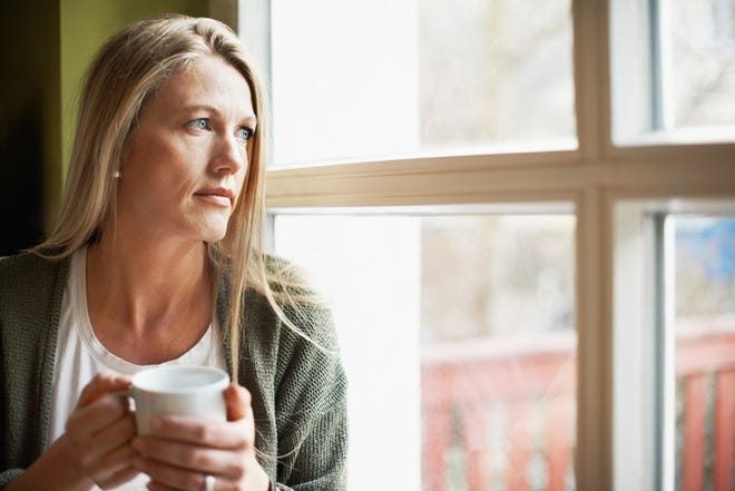 A pensive woman looking out the window while holding a cup of coffee