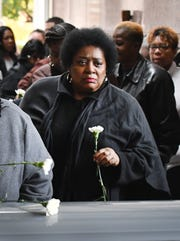 Lucille Donaldson places a flower on the coffin where her mother Gladys Donaldson will finally be put to rest.