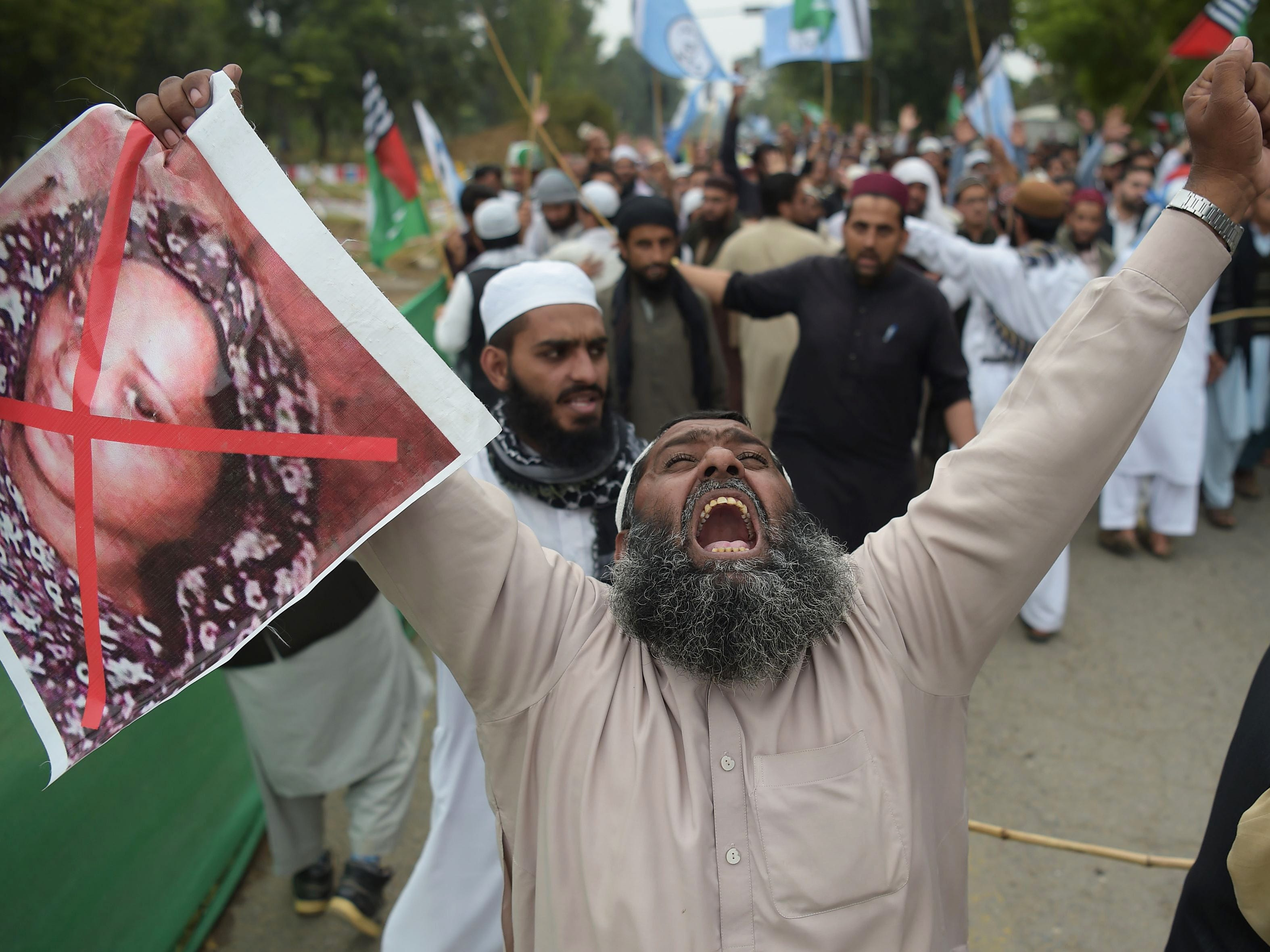 A Pakistani supporter of the Ahle Sunnat Wal Jamaat, a hardline religious party, holds an image of Christian woman Asia Bibi during a protest rally following the Supreme Court's decision to acquit Bibi of blasphemy, in Islamabad on November 2, 2018.
