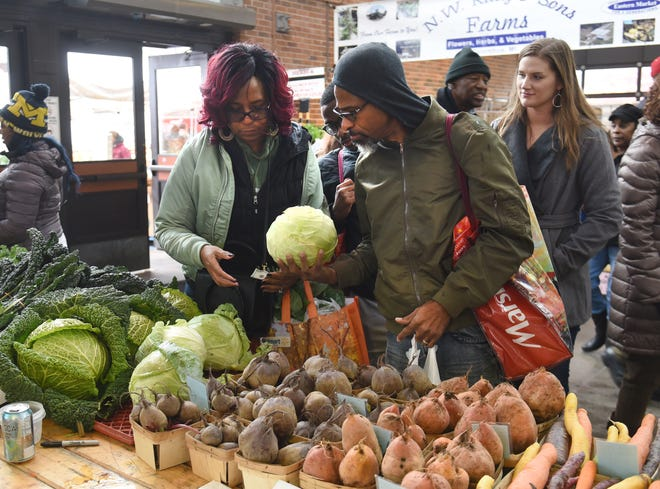 Annaya Watkins and her husband Michael buy produce at Eastern Market on October 27.