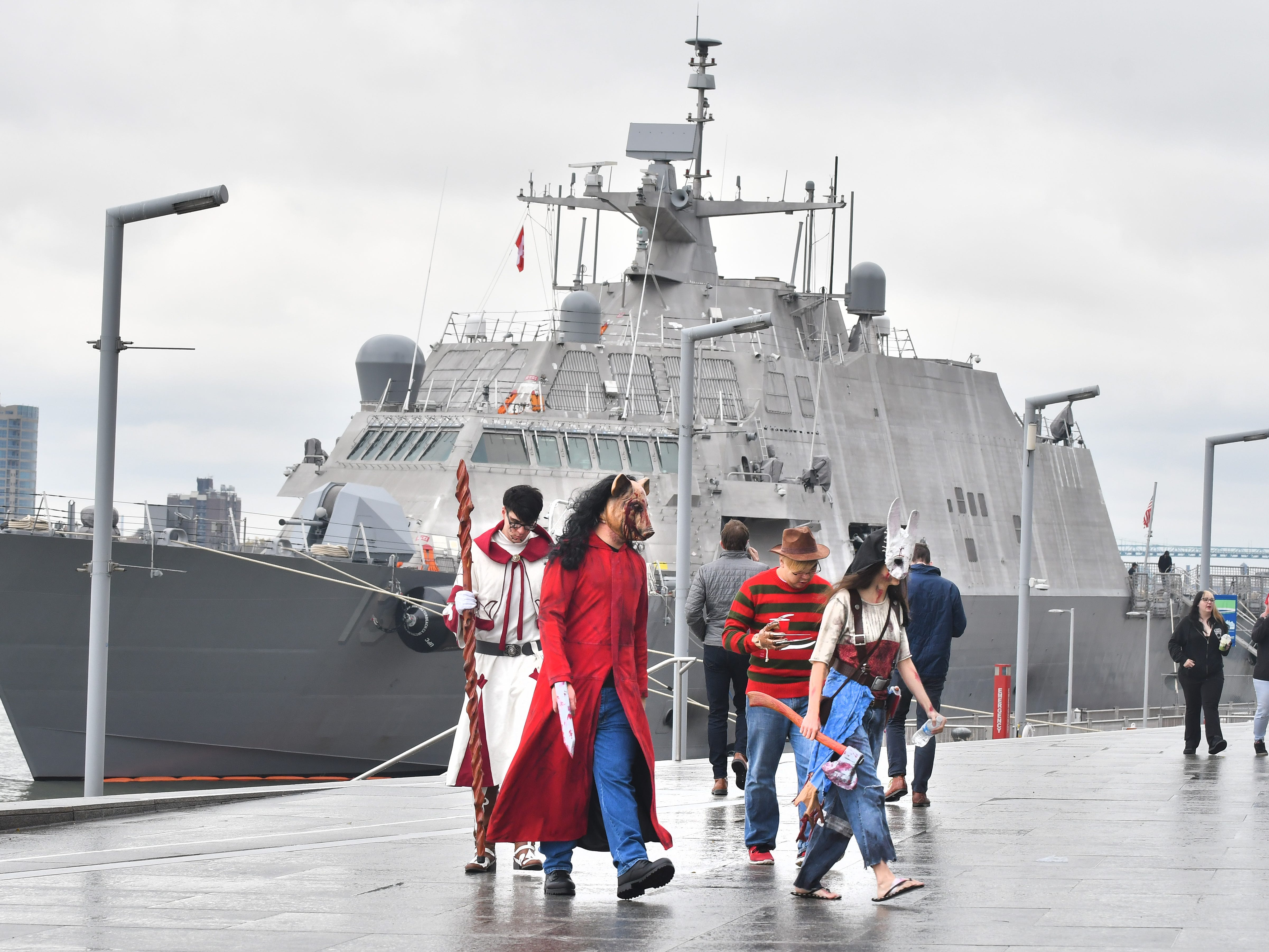 Participants in the 2018 Youmacon at Cobo Center walk along the Detroit Riverwalk past the USS Wichita (LCS-13), a Freedom-class littoral combat ship of the U.S. Navy temporarily docked behind the Renaissance Center. From left, Trevor Russ as a White Mage from Final Fantasy, Paul Krotine as The Pig and Amanda Stanglewicx as The Huntress from Dead by Daylight, and Joe Chuang as Freddie Krueger.