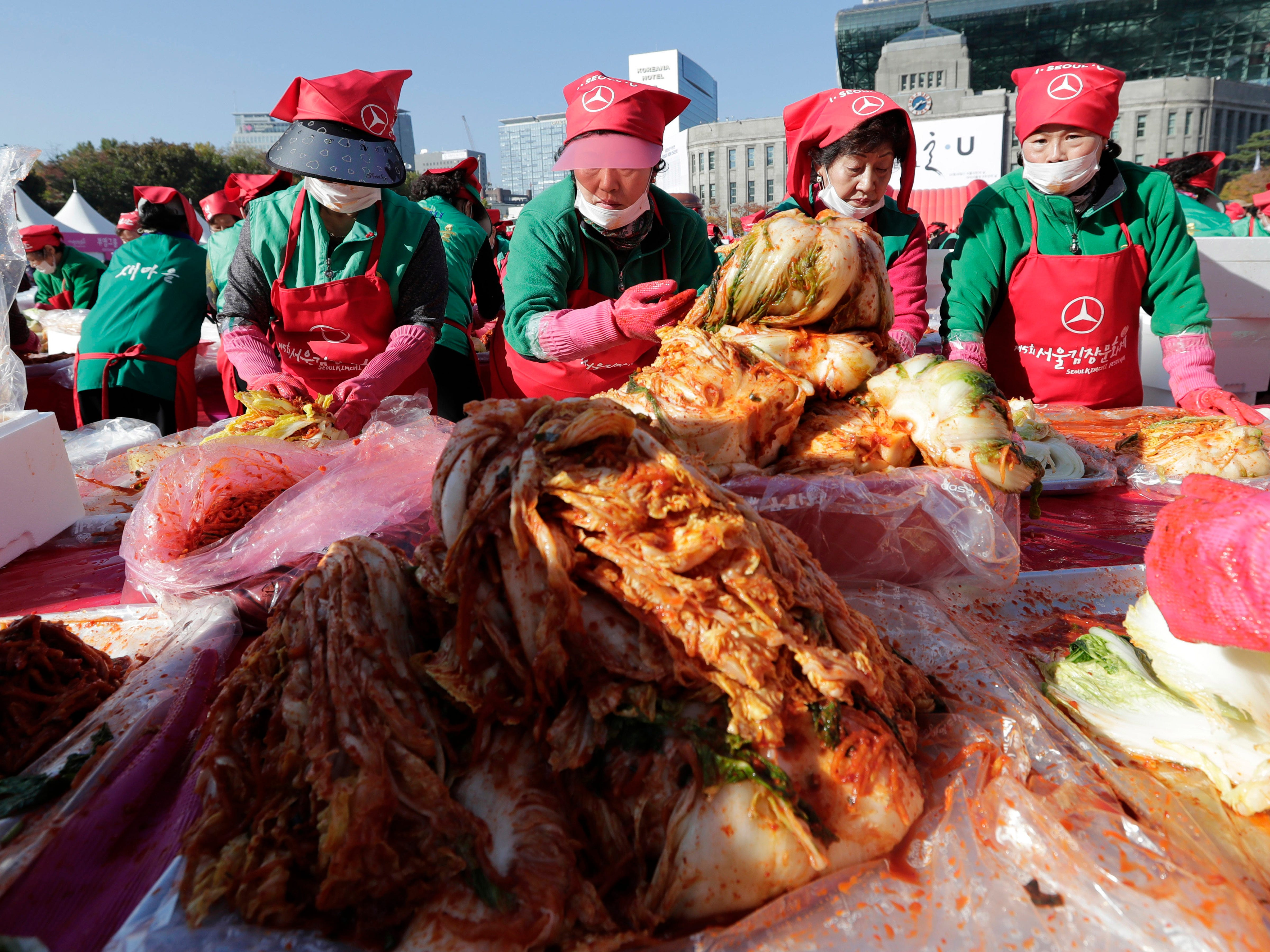 Participants make kimchi, a staple Korean side dish made of fermented vegetables, to donate to needy neighbors in preparation for the winter season during the Seoul Kimchi Festival at Seoul Plaza in Seoul, South Korea, Friday, Nov. 2, 2018. Thousands of people will make kimchi with 165 tons of cabbage during the festival, which runs through Nov. 4.