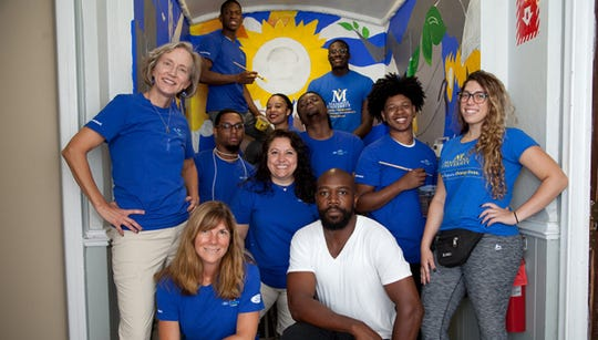 Madonna University faculty and students with artist Hubert Massey, center, and the mural they created at St. Peter's Episcopal Church.