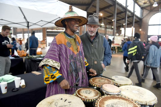 Dan Carmody, right, president of Eastern Market Corp., watches Efe Bes perform a drum solo in Shed 3 at Eastern Market on Saturday October 27, 2018. Max Ortiz, The Detroit News