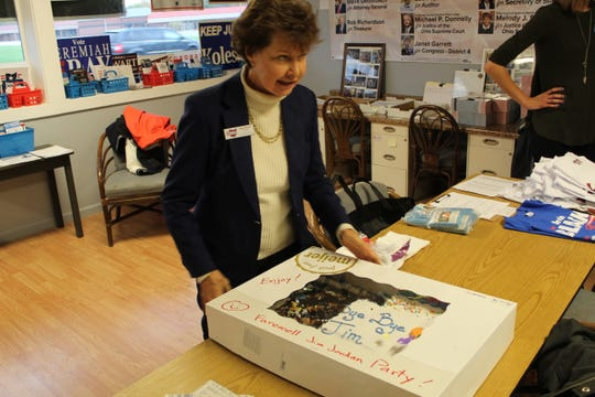 Janet Garrett, Democratic candidate in the U.S. 4th Congressional District race, begins to dish out pieces of cake from a mock farewell party for her opponent, Republican incumbent Rep. Jim Jordan, R-Urbana, at a rally Friday at Sandusky County Democratic Party headquarters.