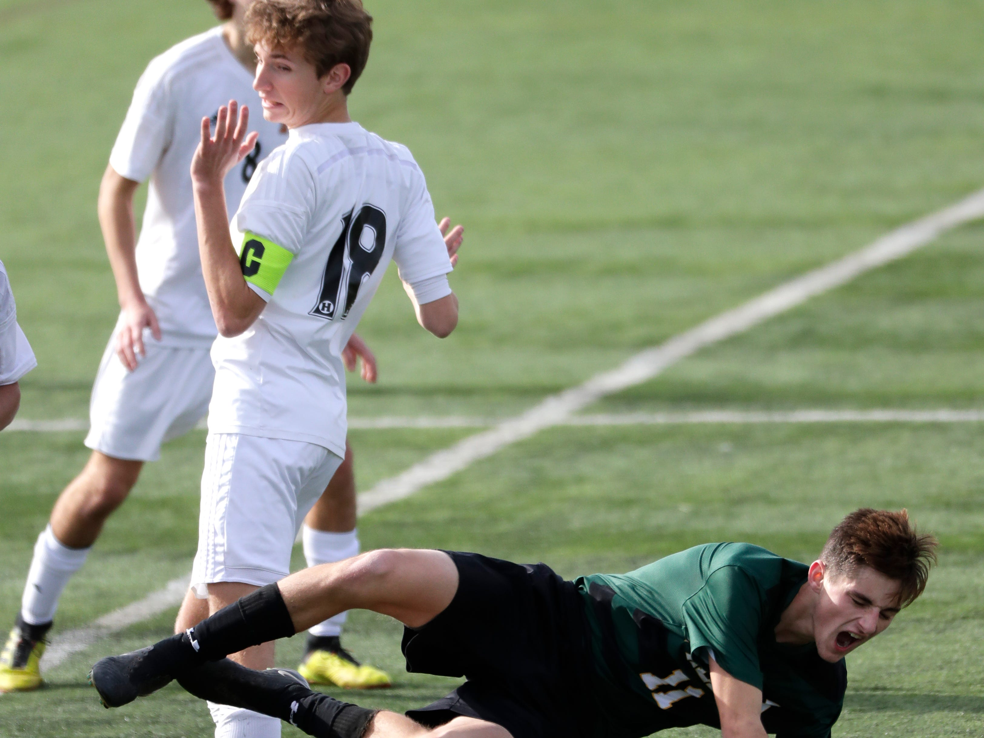 Green Bay Preble High School's Henry Starks (11) is tripped up by Hamilton High School's Caden Etzel (18) during their WIAA Division 1 state semifinal boys soccer game Friday, November 2, 2018, at Uihlein Soccer Park in Milwaukee, Wis.