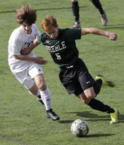 Green Bay Preble's Brian Martinez (5) heads upfield against Hamilton's Steven Arthur during a WIAA Division 1 boys soccer state semifinal Friday at Uihlein Soccer Park in Milwaukee.