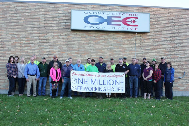 Employees of Oconto Electric Coopertive stand next to the utility's building in Oconto Falls holding  a banner to mark passing more than 1 million hours worked without a lost-time accident.