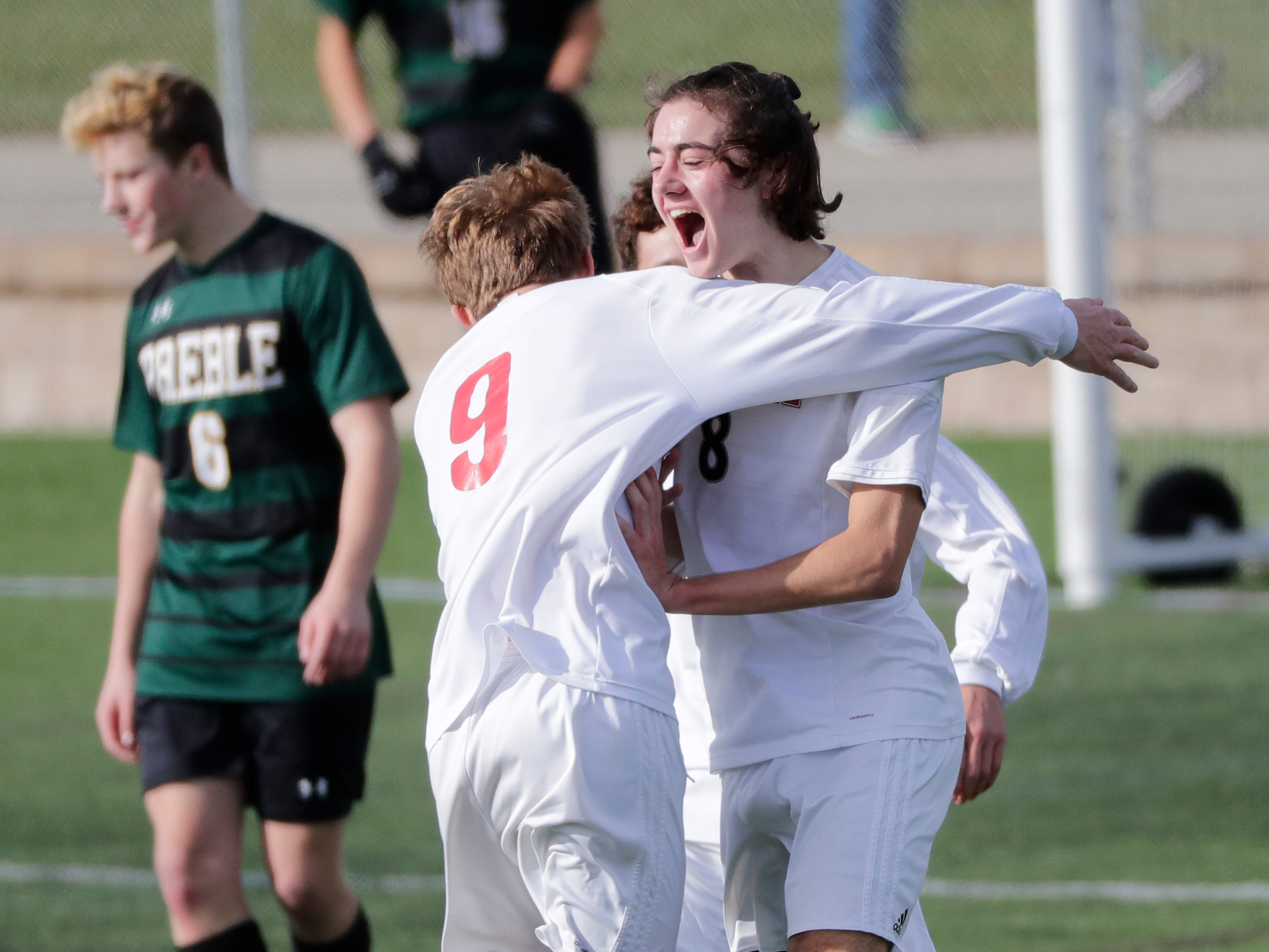 Hamilton High School's Matt Polzer (9) congratulates Zach Wilcox (8) after he scored a goal against Green Bay Preble High School's goalie Noah Conard during their WIAA Division 1 state semifinal boys soccer game Friday, November 2, 2018, at Uihlein Soccer Park in Milwaukee, Wis.