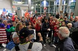 Crowds of people welcome 70 Veterans home from an honor flight to Washington D.C. at Austin Straubel International Airport on in Green Bay, Wisconsin.