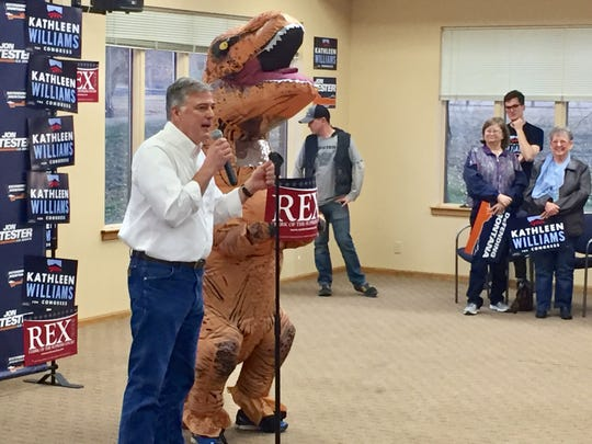Rex Renk, Democratic candidate for Montana State Supreme Court clerk, stands by his T-Rex mascot at a recent Democratic rally In Great Falls.