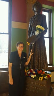 "After voting, historian Martha Kohl paused at the Montana Capitol's statue of Jeannette Rankin, a suffragist and first woman elected to Congress. Others left flowers and ""I Voted"" stickers in tribute."