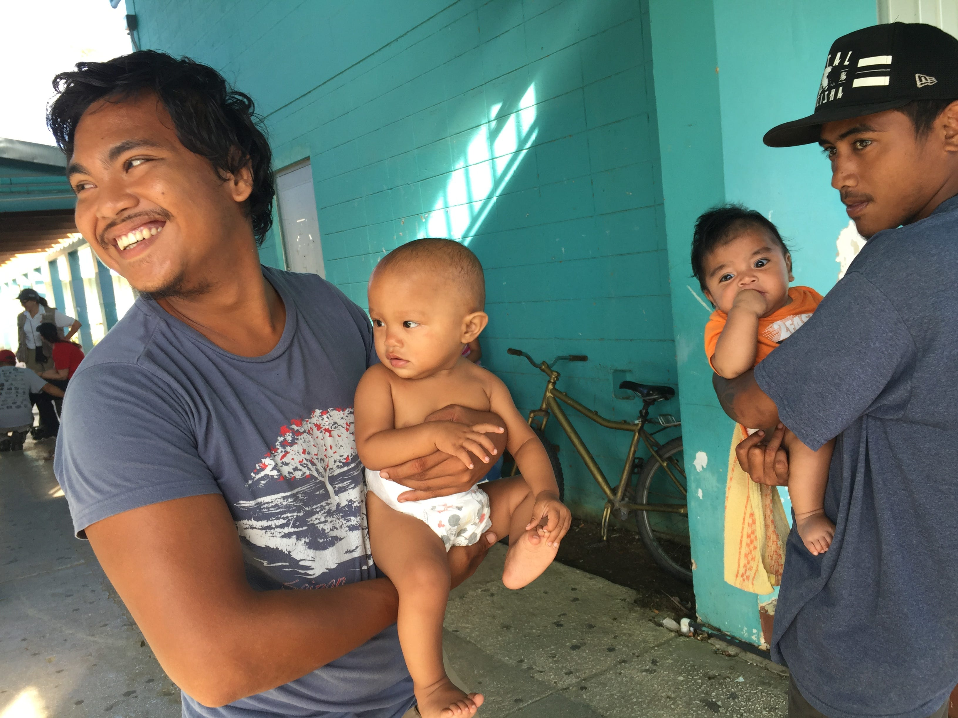 Larry Ada, 20, left, and his daughter Emylinn, 9 months, enjoy a light moment with relatives Greg Angui, 20, right, and Daniel Acosta, 7 months, at Marianas High School on Saipan. The extended family remained sheltered on Nov. 1, 2018, a week after Super Typhoon Yutu.