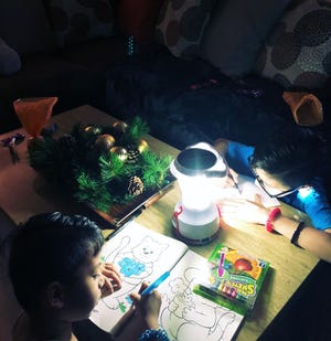 With no power, television and other electronic gadgets, children on typhoon-ravaged Saipan make use of portable lamps to pass away time at night such as drawing and coloring.