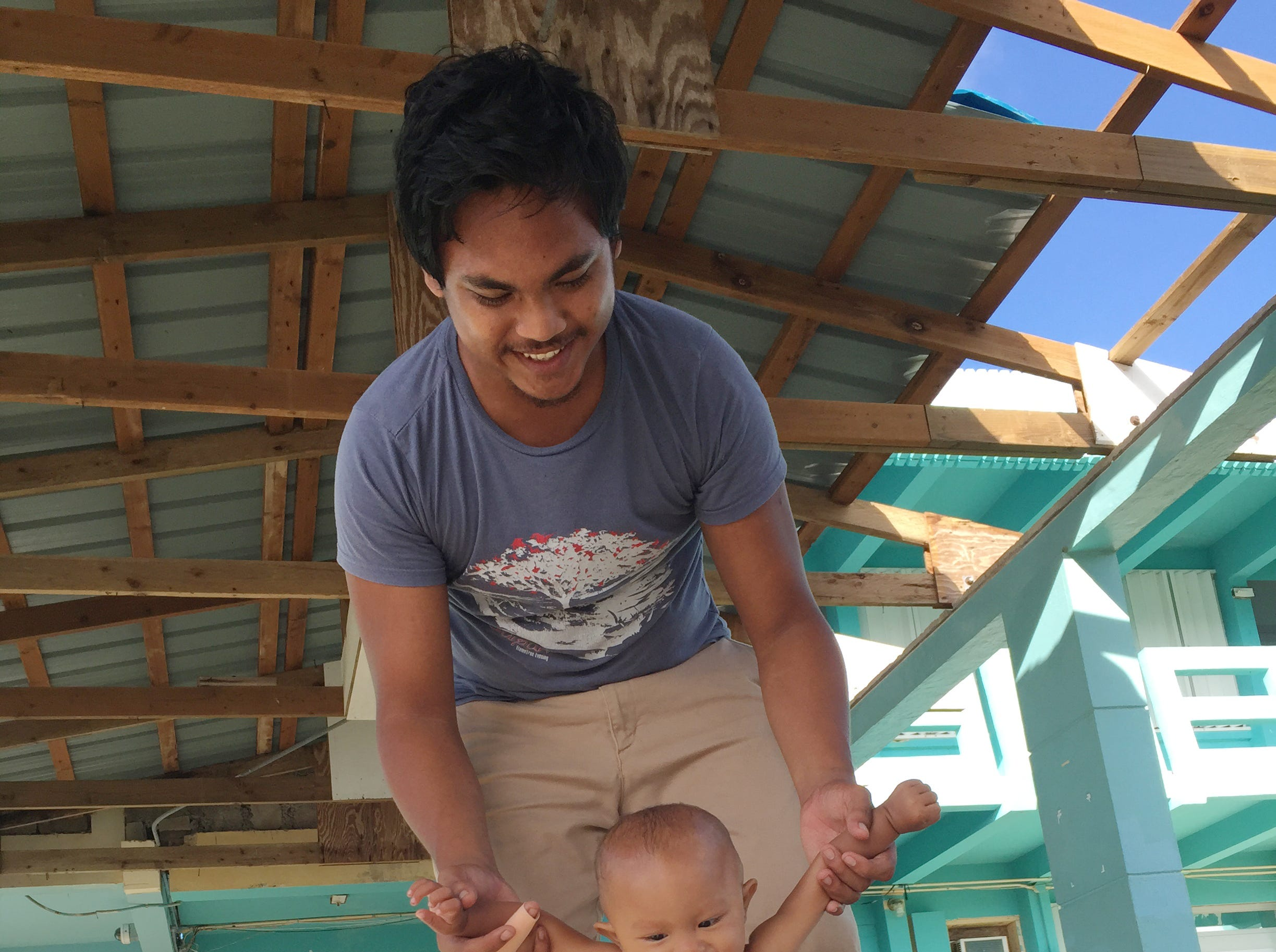 Larry Ada, 20, helps his 9-month-old daughter Emylinn walk at Marianas High School on Saipan, where they remained sheltered on Nov. 1, 2018, a week after Super Typhoon Yutu. Emylinn was a premature baby and small for her age, and she's still learning to crawl, her father said.