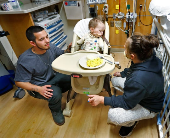 Jeremiah Cox, center, eats with the help of his parents Nicholas Thompson and Ashley Cox, at Riley Hospital for Children.