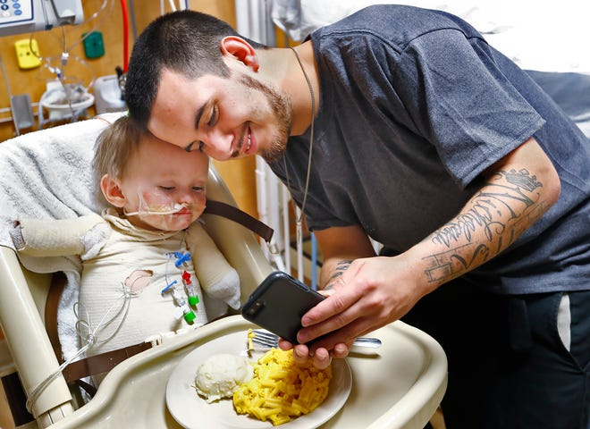 Jeremiah Cox, left, poses poses for a selfie with his father Nicholas Thompson, at Riley Hospital for Children.