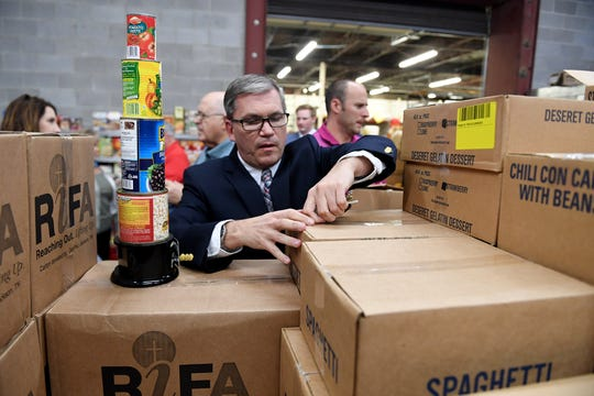 First Counselor of the North State of the Church of Jesus Christ of Latter Day Saints opens up one of the boxes of food donated to Regional Inter-faith Association (RIFA), Friday, November 2.
