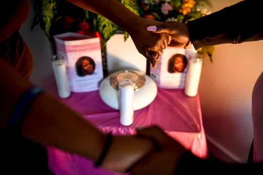 Alicia Hasell, left, holds the hands of her daughter Ashley, right, in front of a memorial with the ashes of her daughter she lost to domestic violence, Amanda, at Hassell's home in Jackson, Tenn., on Friday, Nov. 2, 2018.