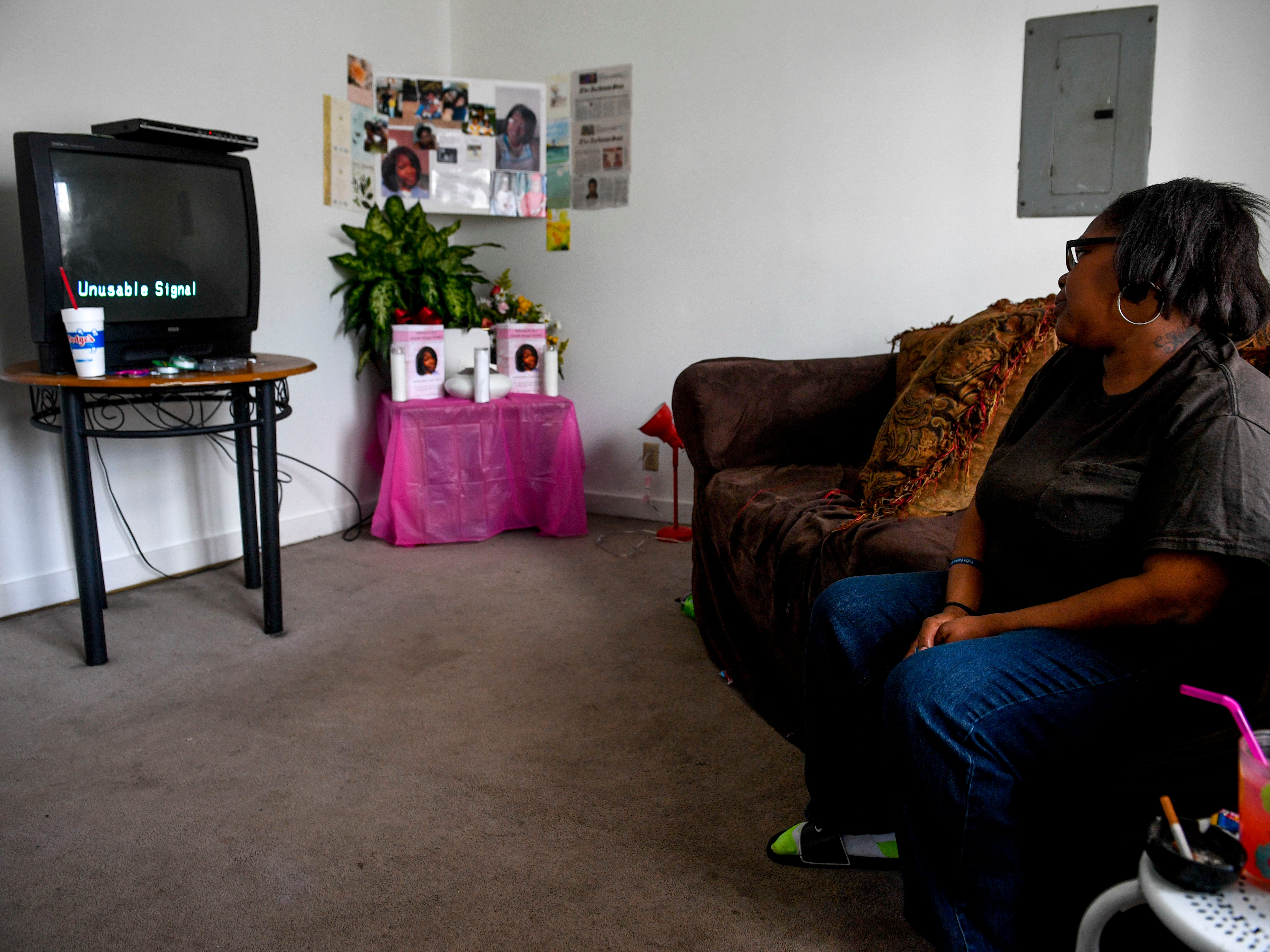 Alicia Hassell sits on the couch and gazes at the ashes of her daughter Amanda Northern, a victim of domestic violence, arranged as part of a memorial at Hassell's home in Jackson, Tenn., on Friday, Nov. 2, 2018.