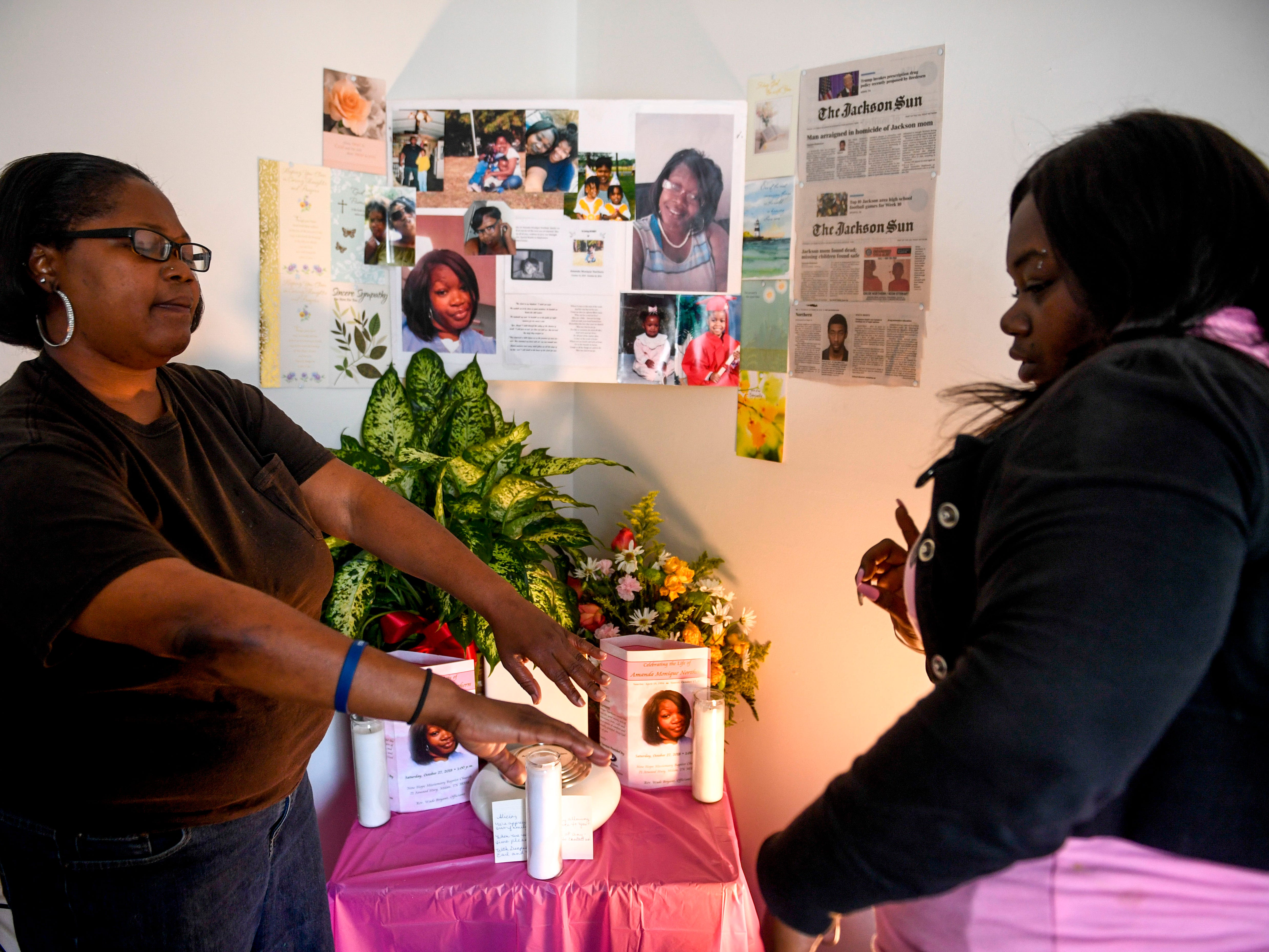Alicia Hassell stretches out her hands to join with her daughter Ashley in front of a memorial for her daughter she lost to domestic violence, Amanda, at Hassell's home in Jackson, Tenn., on Friday, Nov. 2, 2018.