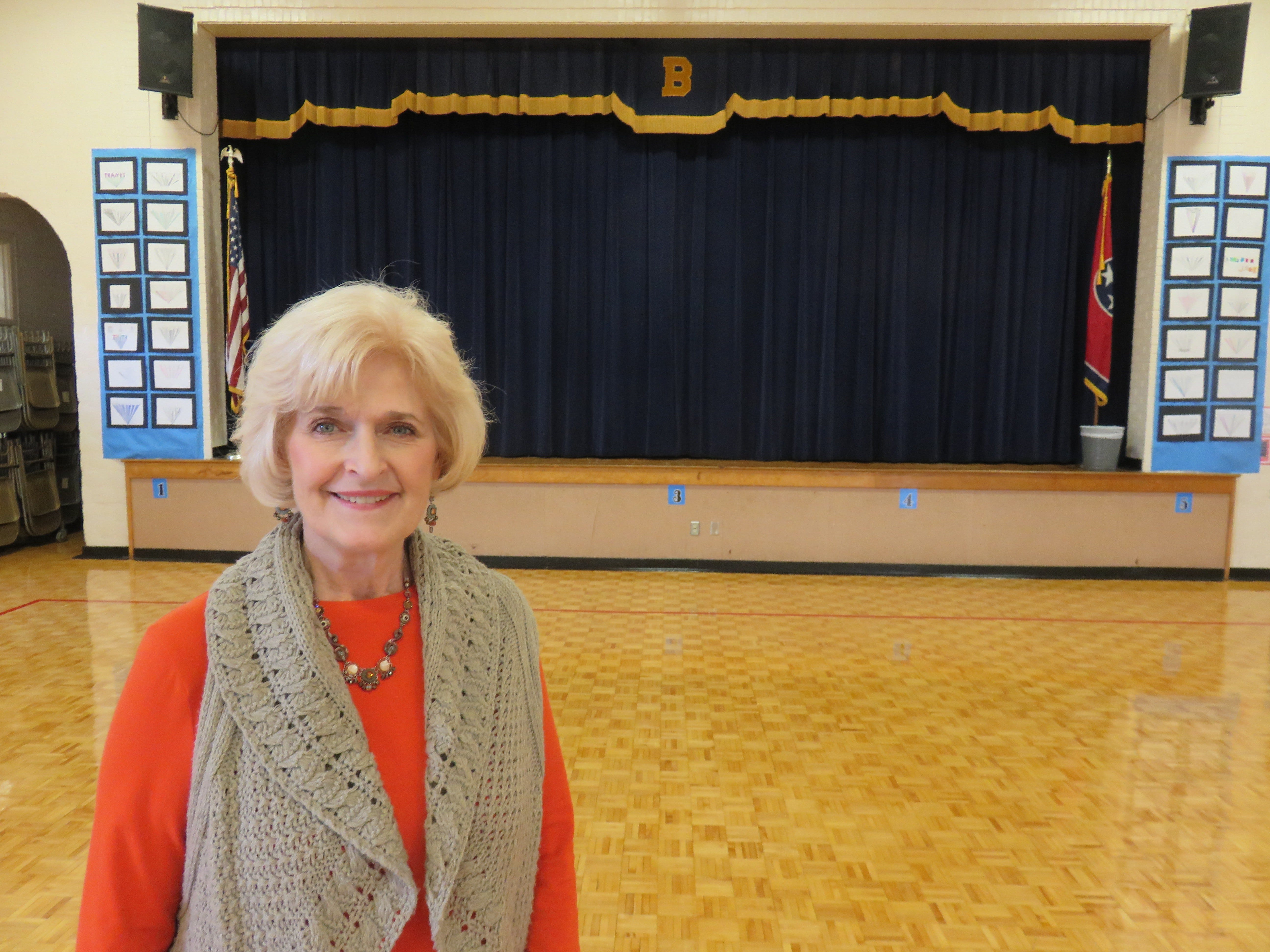 Principal Susan Dunlap in front of gym stage.