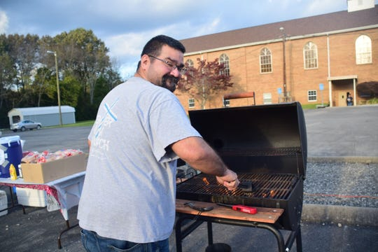 Josh Berlin, youth pastor, shows off his grilling skills during Trunk or Treat held at Center Faith Church on Sunday, Oct. 28.