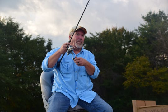 Pastor Barry Mayfield sends out a fishing line loaded with candy to eager Trick or Treaters waiting below during Trunk or Treat held at Center Faith Church Sunday Oct. 28.