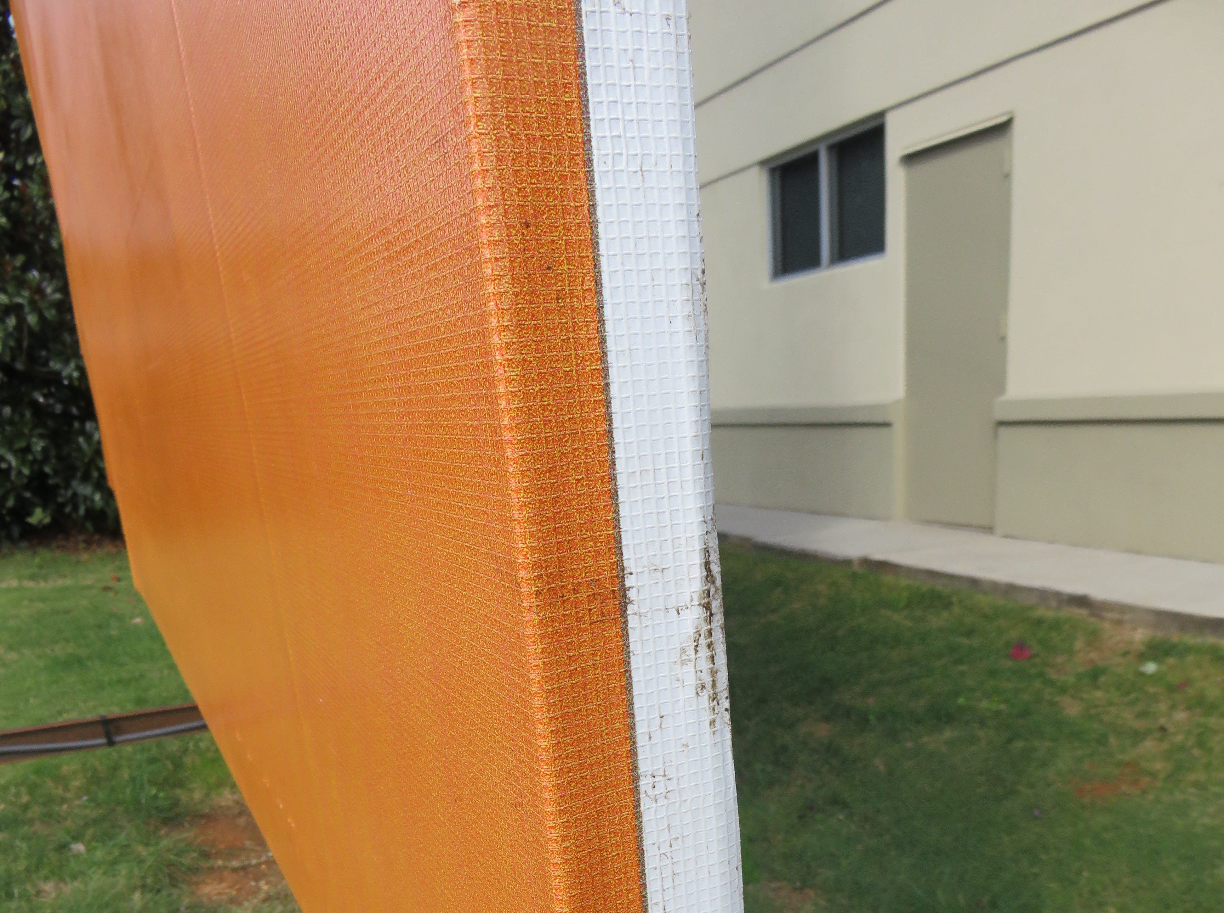 Metallic base of billboard sign has durable material over it to create orange color.