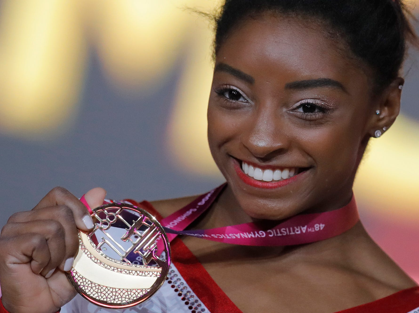 Simone Biles of the U.S. shows her gold medal after the women's vault final on the first day of the apparatus finals of the of the Gymnastics World Chamionships at the Aspire Dome in Doha, Qatar, Friday, Nov. 2, 2018. (AP Photo/Vadim Ghirda)