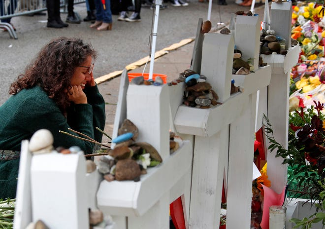 Anat Halevy Hochberg, of Brooklyn, NY., visits a makeshift memorial outside the Tree of Life synagogue where 11 people were killed on Oct. 27 while worshipping, in the Squirrel Hill neighborhood of Pittsburgh, Thursday, Nov. 1, 2018. (AP Photo/Gene J. Puskar)