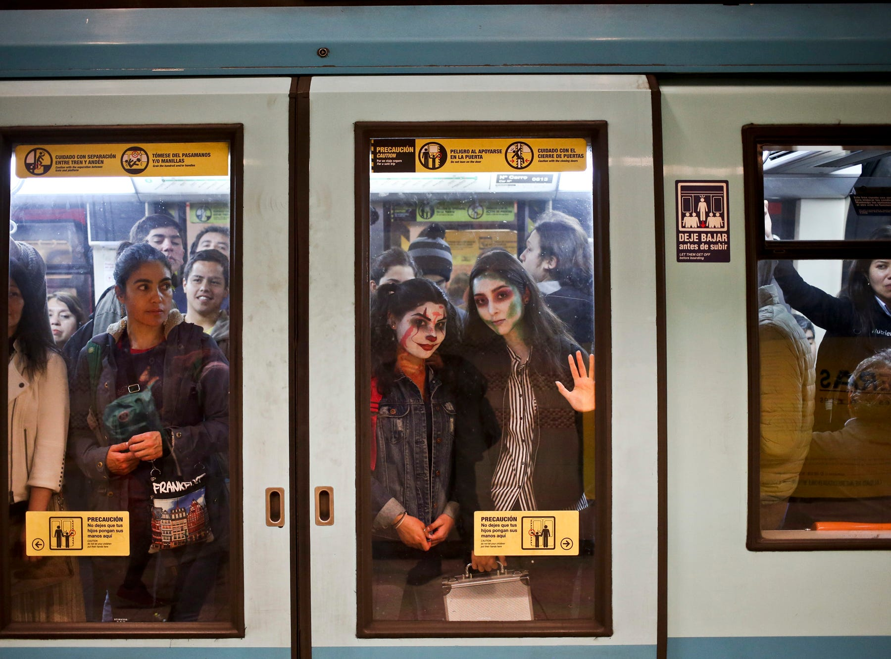 Young women, with their faces painted as a clown and zombie for Halloween, travel in the subway in Santiago, Chile, Tuesday, Oct. 30, 2018. (AP Photo/Esteban Felix)
