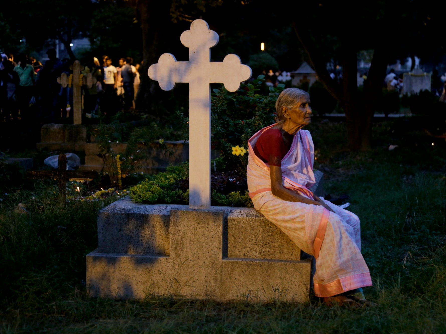 An elderly Indian Christian woman sits on a grave of her relative to pay tribute on All Souls Day in Kolkata, India, Friday, Nov. 2, 2018. The day honors the dead as friends and families gather in cemeteries to decorate graves of loved ones with candles and flowers and offer prayers. (AP Photo/Bikas Das)